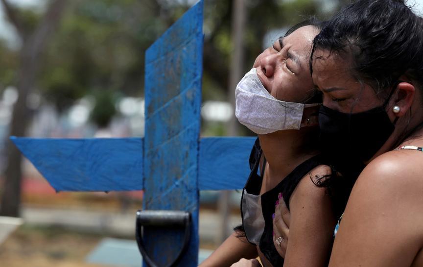 Hai người phụ nữ khóc khi mất người thân vì Covid-19 tại Manaus, Brazil hồi tháng một. Ảnh: Reuters.