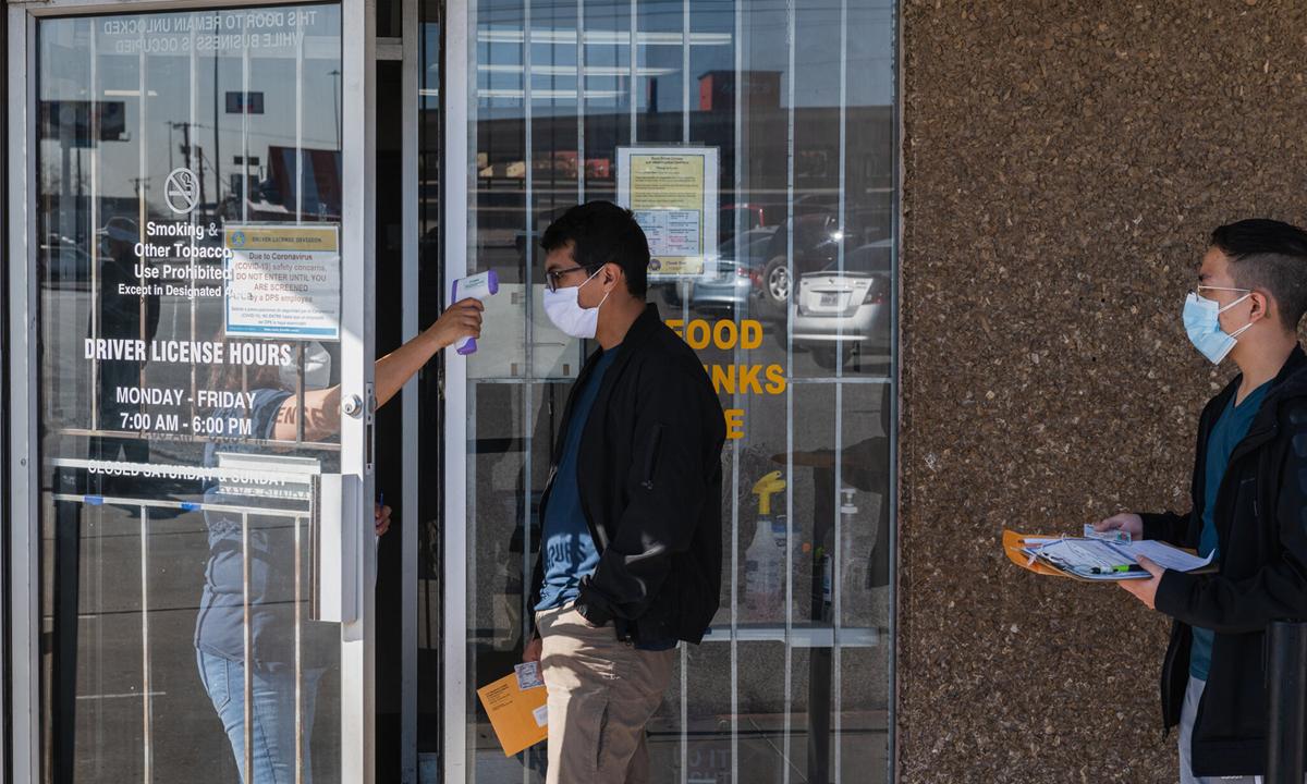 Một người đeo khẩu trang được kiểm tra thân nhiệt trước khi vào trụ sở chính quyền ở thành phố El Paso, bang Texas hôm 10/3. Ảnh: NYTimes.