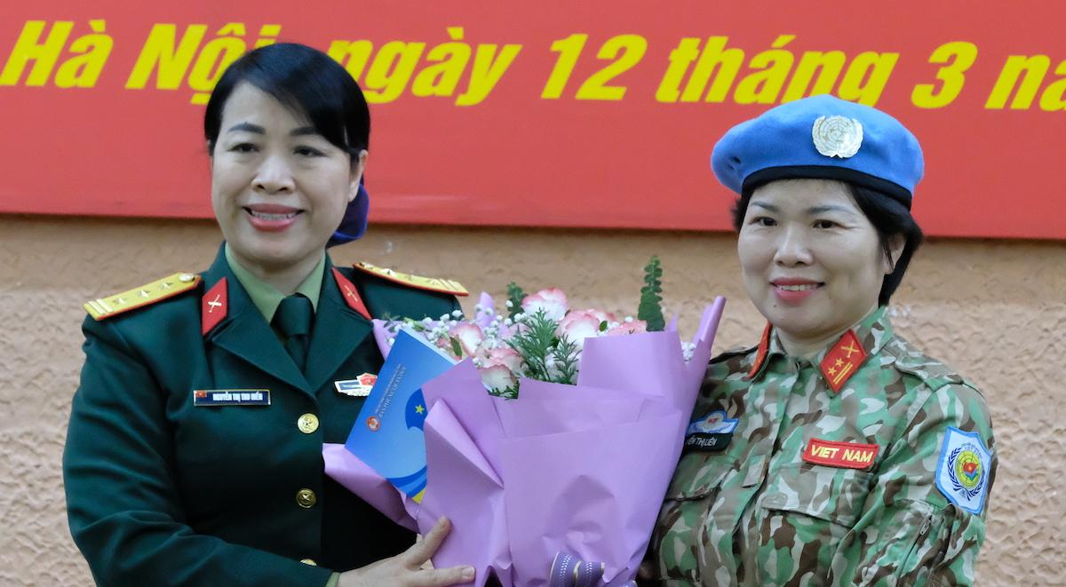 Trung tá Nguyễn Thị Liên nhận hoa chúc mừng từ Thượng tá Nguyễn Thị Thu Hiền, Phó Trưởng Ban Phụ nữ Quân đội sáng 12/3. Ảnh: Hoàng Thùy