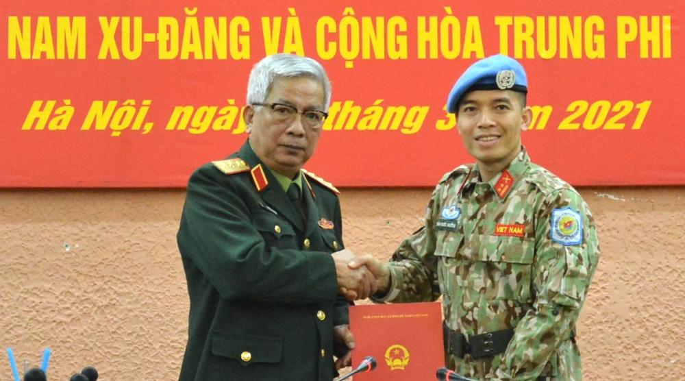 Thượng tướng Nguyễn Chí Vịnh, Thứ trưởng Quốc phòng trao quyết định của Chủ tịch nước cho trung tá Trần Đức Hưởng, sáng 12/3. Ảnh: Hoàng Thùy