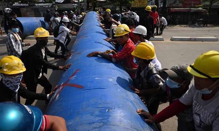 Người biểu tình di chuyển một đường ống lớn để dựng rào chắn tại thành phố Yangon hôm 11/3. Ảnh: AFP.