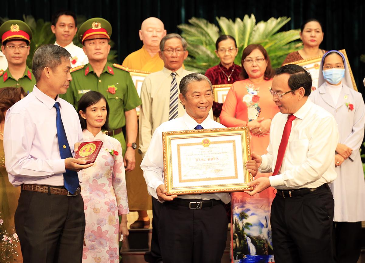 Bí thư Thành uỷ Nguyễn Văn Nên tặng bằng khen tuyên dương những tấm gương người tốt, việc tốt. Ảnh: Hữu Công.