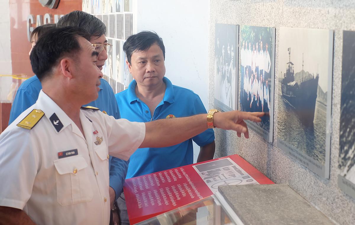 Cựu binh Gạc Ma Lê Văn Thoa (bên trái) giới thiệu các đồng đội của mình qua ảnh. Ảnh: An Phước.