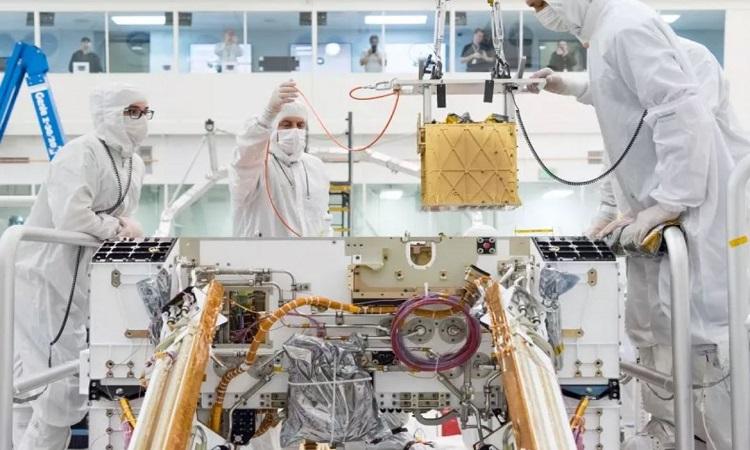 Các nhà nghiên cứu lắp MOXIE dưới bộ khung gầm của robot Perseverance. Ảnh: NASA.