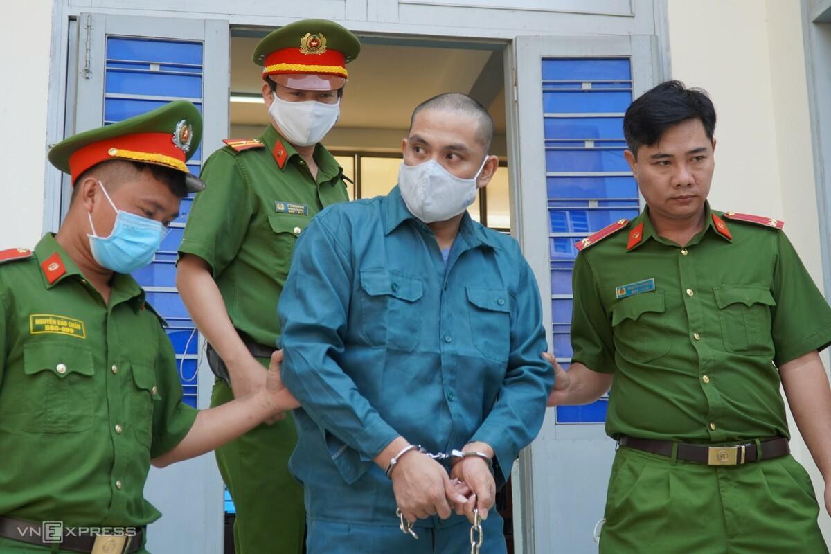 Cảnh sát đưa bị cáo Nam ra xe đi thụ án. Ảnh: Việt Quốc.