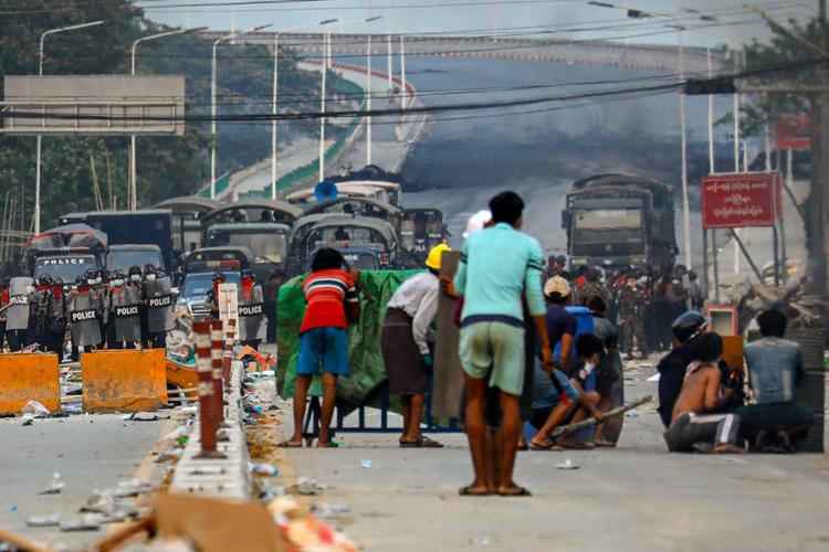 Người biểu tình núp sau những tấm khiên tự chế khi đối đầu lực lượng an ninh tại Hlaingthaya, ngoại ô Yangon hôm 14/3. Ảnh: AFP.