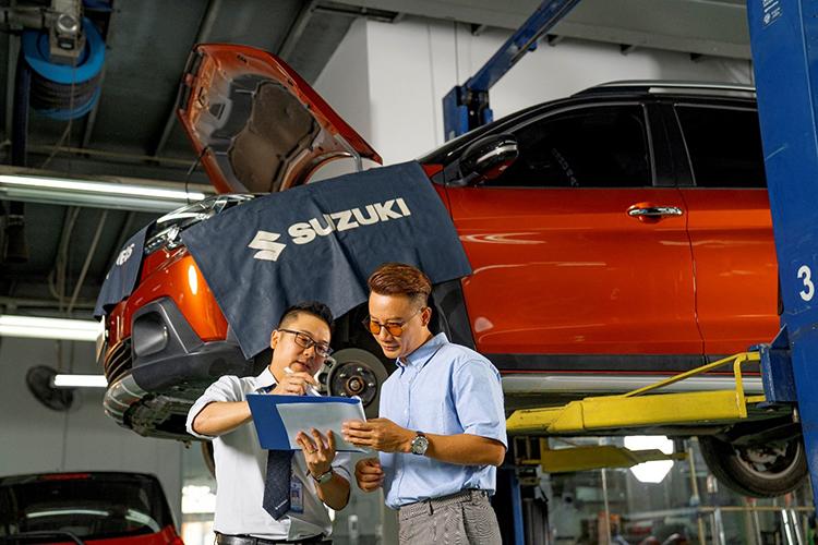 Nhân viên một đại lý Suzuki (áo trắng) hướng dẫn khách làm bảo dưỡng xe.