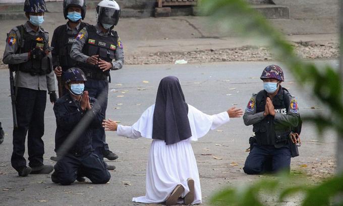 Nữ tu Ann Rose quỳ trước cảnh sát ở thành phố Myitkyina, bang Kachin, hôm 8/3, trong khi hai cảnh sát cũng quỳ với bà. Ảnh: AFP.