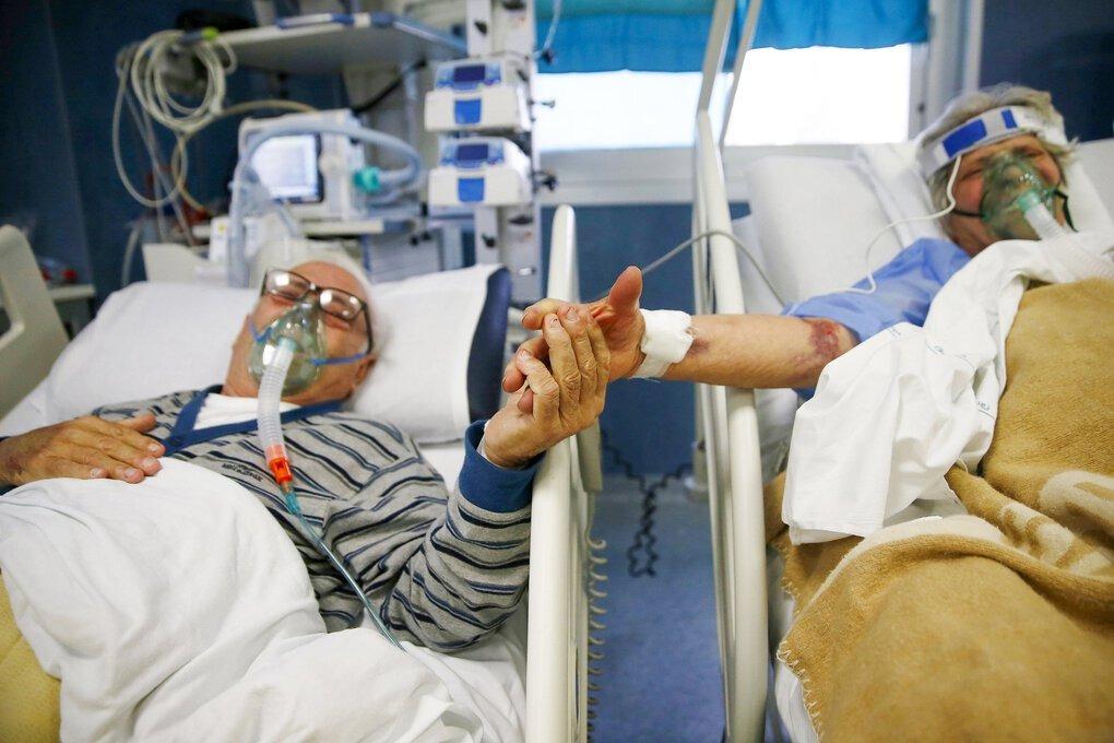 Cặp vợ chồng nắm tay nhau trong khu điều trị tích cực của bệnh viện San Filippo Neri ở Rome hồi đầu tuần. Ảnh: AP.