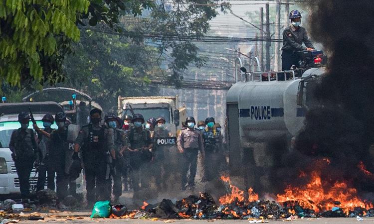 Lực lượng an ninh Myanmar đứng sau một hàng rào đang bốc cháy ở Yangon hôm nay. Ảnh: AFP.