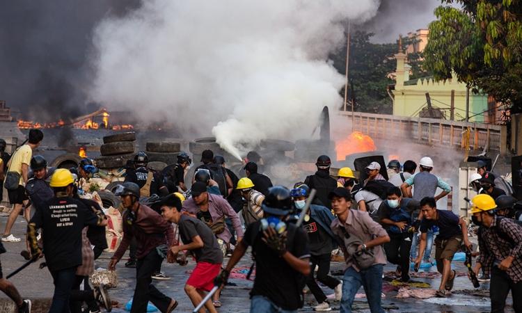 Người biểu tình Myanmar tháo chạy ở thành phố Yangon hôm 16/3. Ảnh: Reuters.
