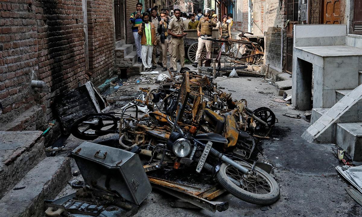 Cảnh sát Ấn Độ chụp ảnh hiện trường xe máy bị đốt trong vụ đụng độ giữa tín đồ đạo Hindu và Hồi giáo ở New Delhi tháng 3/2020. Ảnh: Reuters,.