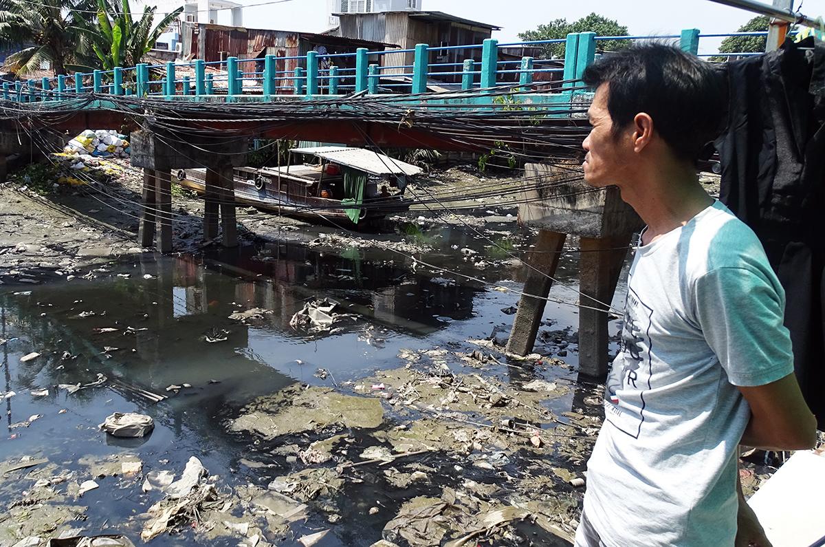 Ông Đức đứng nhìn con kênh ô nhiễm, người dân sống hai bên xả chất thải xuống kênh. Ảnh: Hà An.