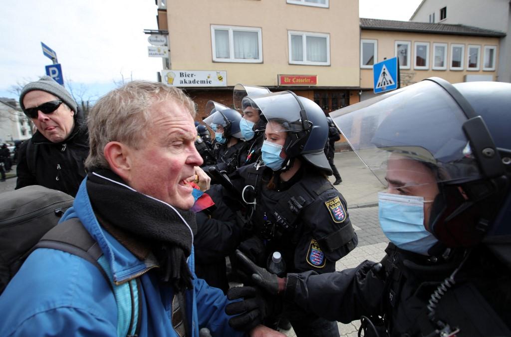 Một người biểu tình tranh cãi với cảnh sát tại Kassel hôm 20/3. Ảnh: AFP.