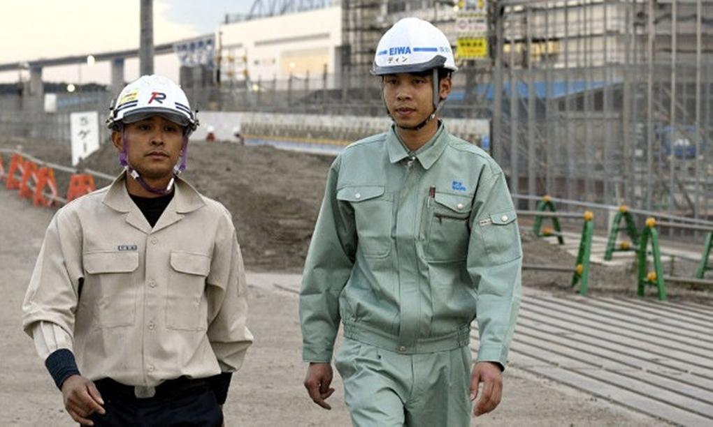 Dinh Van Duyet (phải), một công nhân xây dựng Việt Nam tại công trường thi đấu các môn thể thao dưới nước ở Tokyo năm 2018. Ảnh: Mainichi