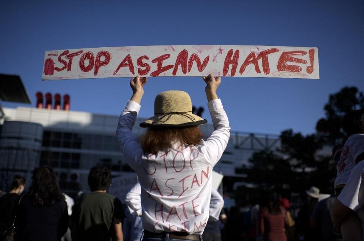 Một người biểu tình mặc áo và giơ biểu ngữ có dòng chữ hãy dừng tội ác thù ghét người gốc Á tại Texas ngày 21/3. Ảnh: AFP.