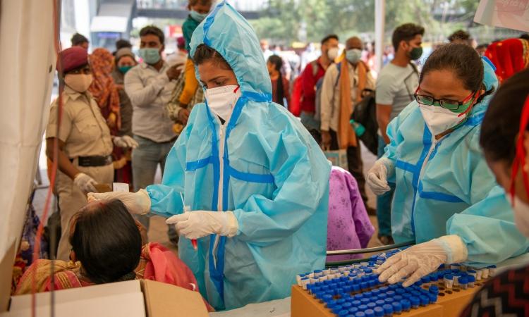 Nhân viên y tế lấy mẫu xét nghiệm cho người dân ở Anand Vihar, Delhi, hôm 21/3. Ảnh: Reuters.