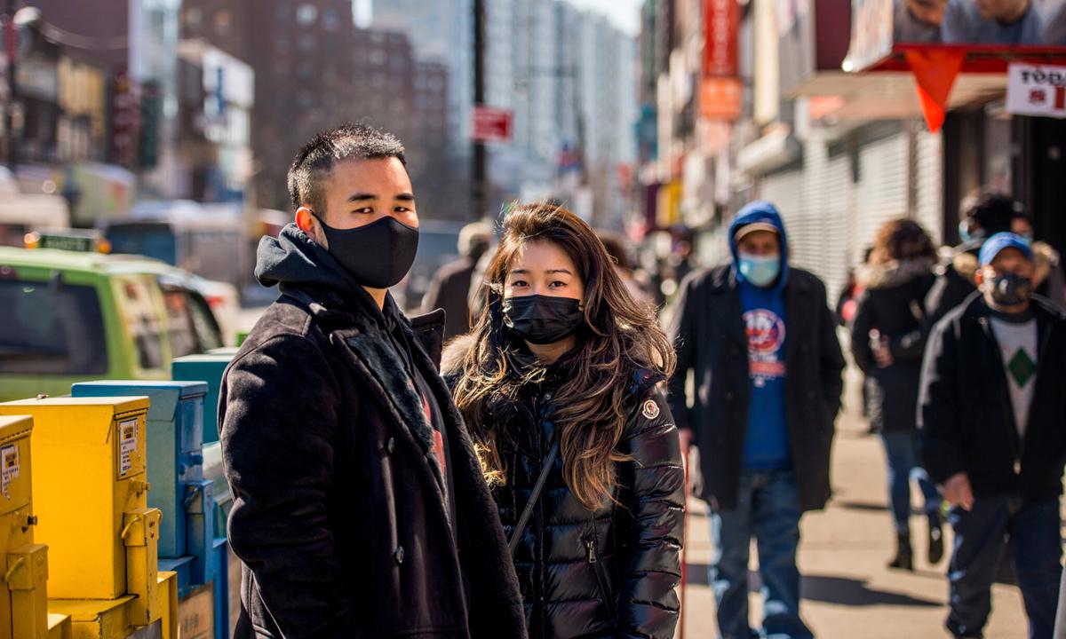 Hai người Mỹ gốc Á trên con phố Flushing, quận Queens, thành phố New York hồi cuối tháng 2. Ảnh: NYTimes.