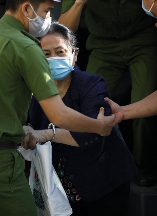 Bà Diệp luôn mang theo túi hồ sơ, tài liệu, được dìu xuống xe tù, vào phòng xét xử. Ảnh: Hữu Khoa.