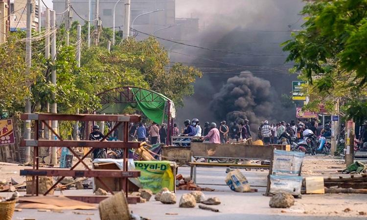 Khói bốc lên từ những rào chắn bị đốt trong biểu tình phản đối đảo chính ở Mandalay, Myanmar hôm 22/3. Ảnh: AFP.