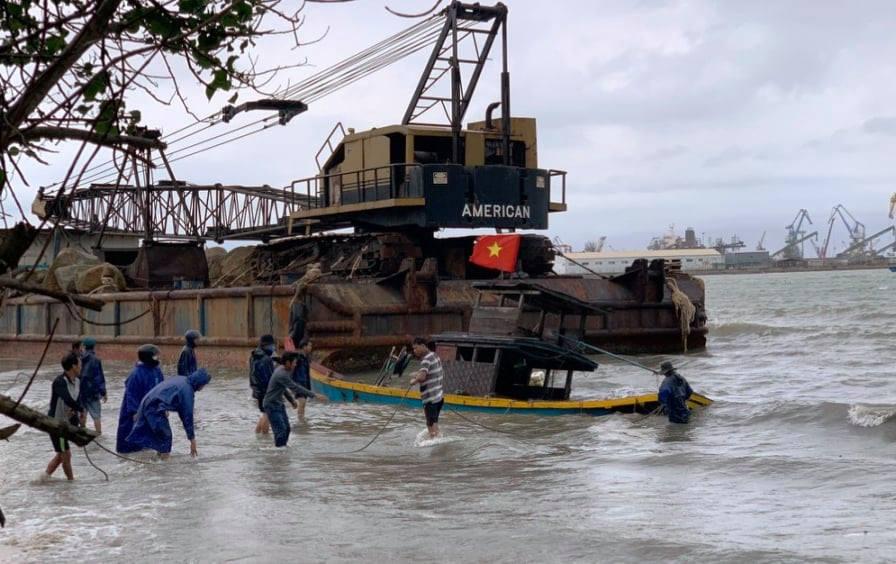 Sà lan trôi dạt vào bờ đâm chìm tàu cá của người dân. Ảnh: Chí Đại.