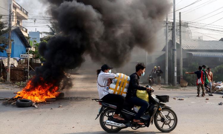 Người dân đi qua rào chắn bị đốt trên đường phố Mandalay trong cuộc biểu tình hôm 22/3. Ảnh: AFP.