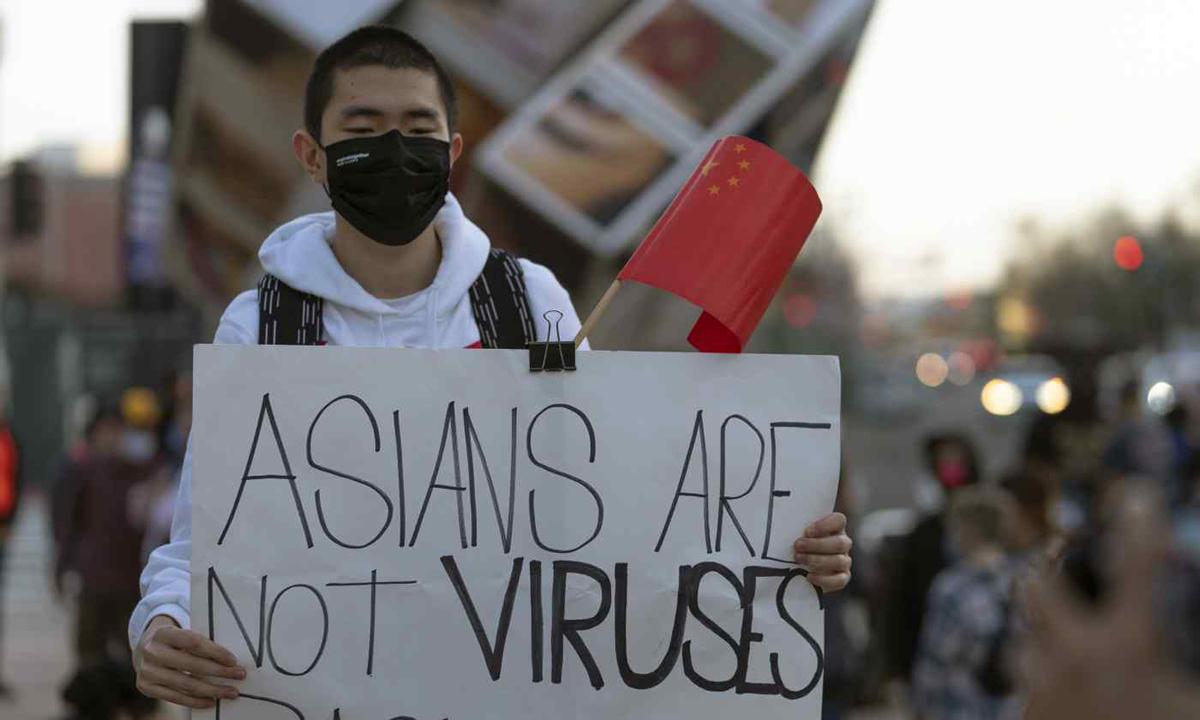 Người biểu tình cầm bảng người châu Á không phải là virus tại Los Angeles hôm 13/3. Ảnh: AP.