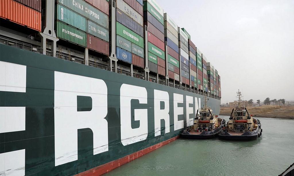 Các tàu kéo cố gắng giải phóng tàu hàng Ever Given mắc kẹt giữa kênh đào Suez hôm 25/3. Ảnh: AFP.