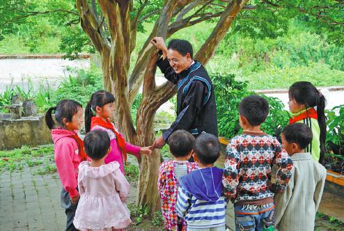Thầy Nong trò chuyện với học sinh tại làng bệnh phong huyện Quảng Nam, Trung Quốc. Ảnh: China Daily.