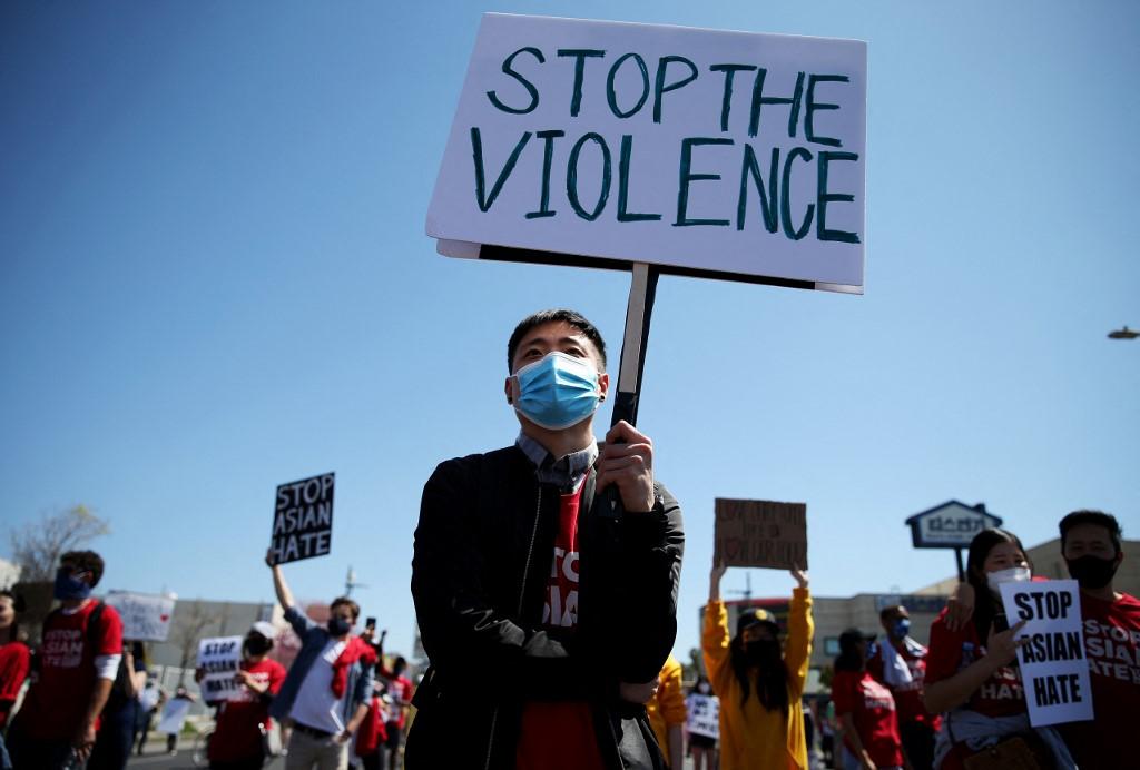Người biểu tình tại Los Angeles giơ biểu ngữ Hãy dừng bạo lực ngày 27/3. Ảnh: AFP.