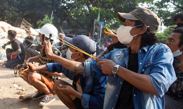 Người biểu tình núp sau rào chắn trong cuộc biểu tình phản đối đảo chính ở Yangon, Myanmar hôm 28/3. Ảnh: Reuters.