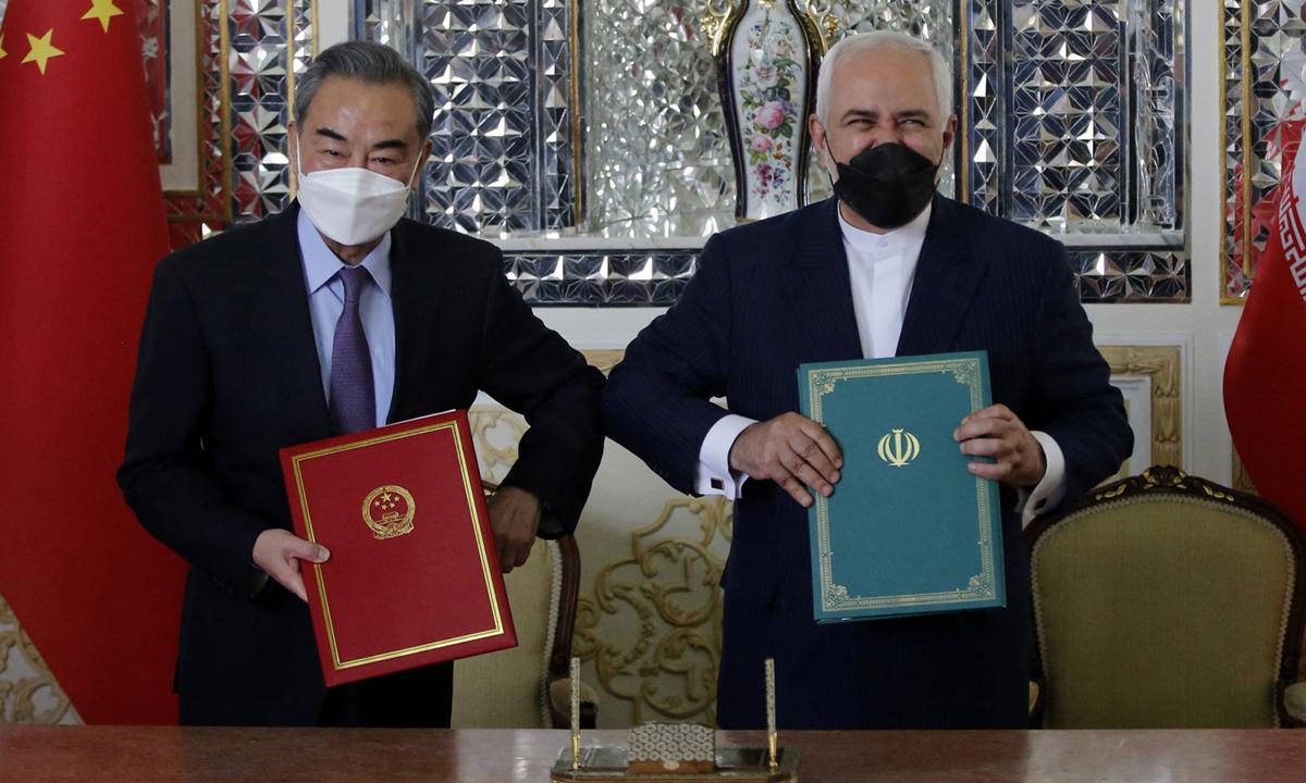Ngoại trưởng Trung Quốc Vương Nghị (trái) và Ngoại trưởng Iran Mohammad Javad Zarif tại lễ ký kết thỏa thuận hợp tác ở Tehran hôm 27/3. Ảnh: AFP.