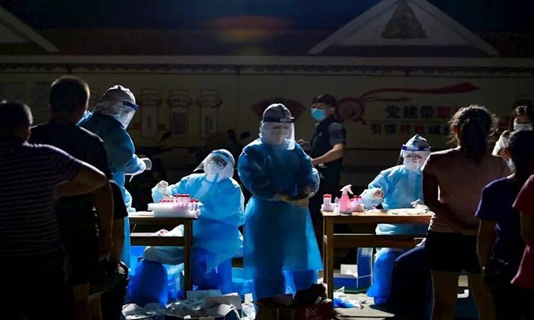 Nhân viên y tế lấy mẫu xét nghiệm Covid-19 cho người dân ở Thụy Lệ, tỉnh Vân Nam, Trung Quốc hôm 30/3. Ảnh: AFP.