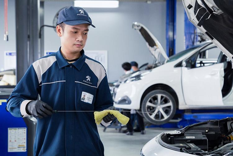 Một kỹ thuật viên Peugeot Việt Nam kiểm tra thăm dầu động cơ.