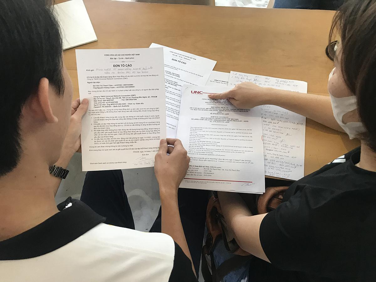 Khách hàng tập hợp hồ sơ tố cáo Công ty UNC. Ảnh: Việt Anh.
