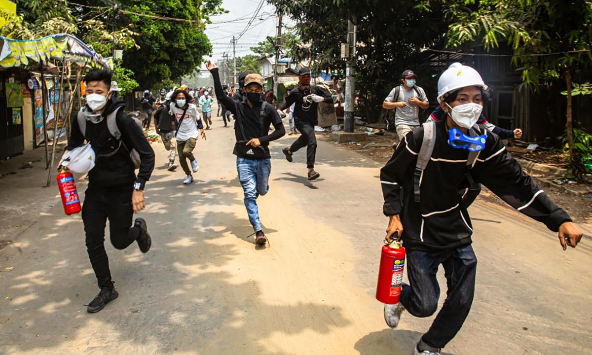 Người biểu tình chạy trốn khi lực lượng an ninh Myanmar trấn áp tại thành phố Monywa ngày 30/3. Ảnh: AFP.