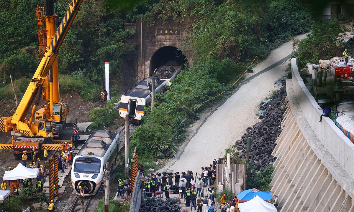 Cần cẩu đưa các toa phía sau đoàn tàu bị trật bánh ra khỏi đường ray tại khu vực huyện Hoa Liên, đảo Đài Loan, ngày 7/3. Ảnh: Reuters.