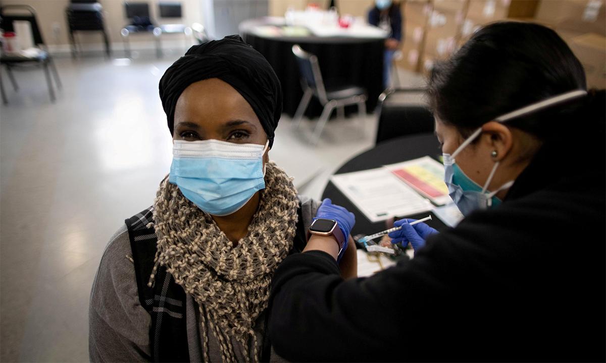 Nhân viên y tế Mỹ tiêm mũi vaccine Covid-19 cho một phụ nữ tại điểm tiêm chủng ở thành phố Los Angeles, bang California, ngày 12/3. Ảnh: Reuters.