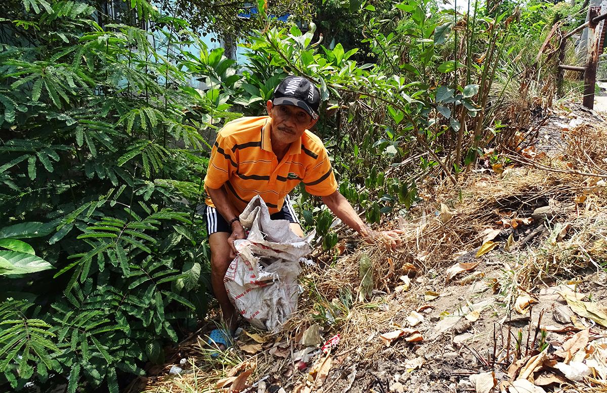 Ông Phạm Văn Đồng vớt rác bị vứt xuống dòng kênh, sáng 1/4. Ảnh: Hà An.