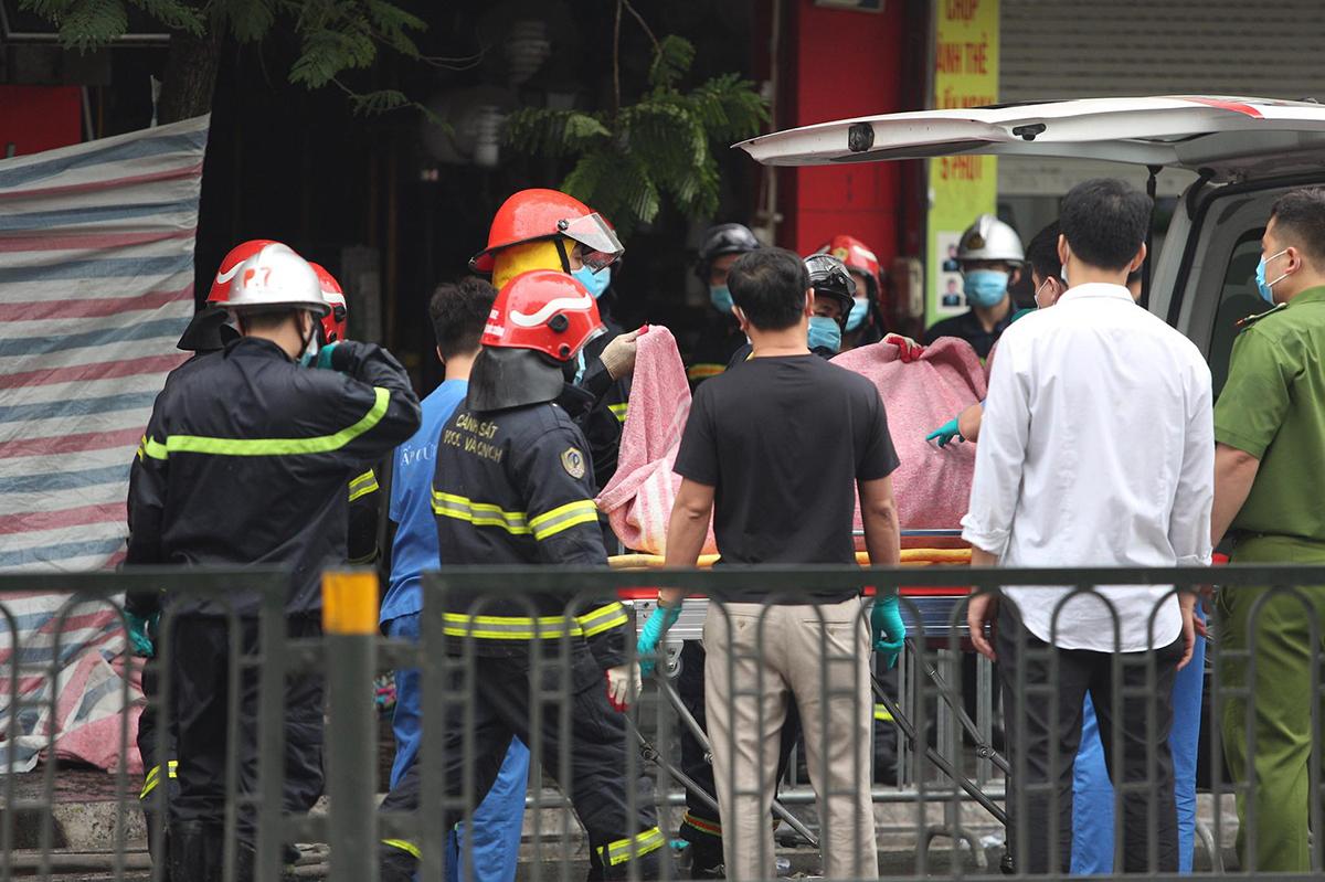 Lực lượng cứu hộ đưa một thi thể ra khỏi ngôi nhà sáng 4/4. Ảnh: Nguyễn Định.