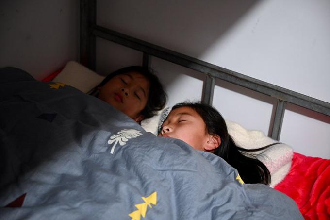 Hai học sinh ngủ trong phòng ký túc xá của trường tiểu học ở tỉnh Phúc Kiến hôm 28/2. Ảnh: Xinhua/Jiang Kehong.