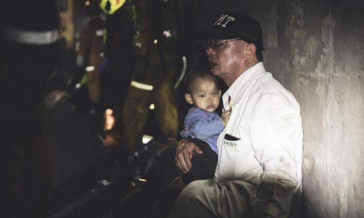 Bác sĩ Wu Kun-chi ôm cậu bé vào lòng vỗ về sau tai nạn đường sắt ở huyện Hoa Liên, Đài Loan hôm 2/4. Ảnh: CNA.