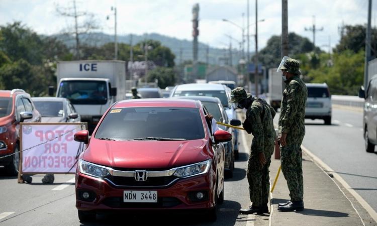 Cảnh sát Philippines kiểm soát xe cộ tại cửa ngõ thành phố Quezon, vùng thủ đô Manila, hôm 29/3. Ảnh: Reuters.