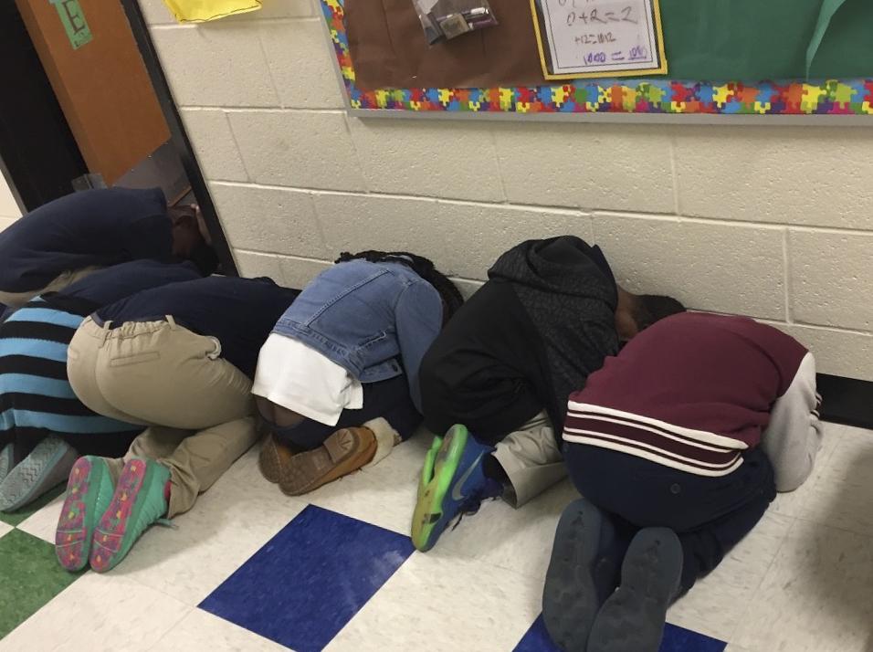 Học sinh lớp cô Hồng iễn tập chống lốc xoáy (tornado drill): cúi gập người, che đầu ở những góc tường ngoài hành lang, xa cửa sổ lớp học. Ảnh: Nhân vật cung cấp.
