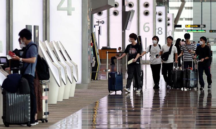 Hành khách tại sân bay Changi, Singapore tháng 3/2020. Ảnh: Reuters.