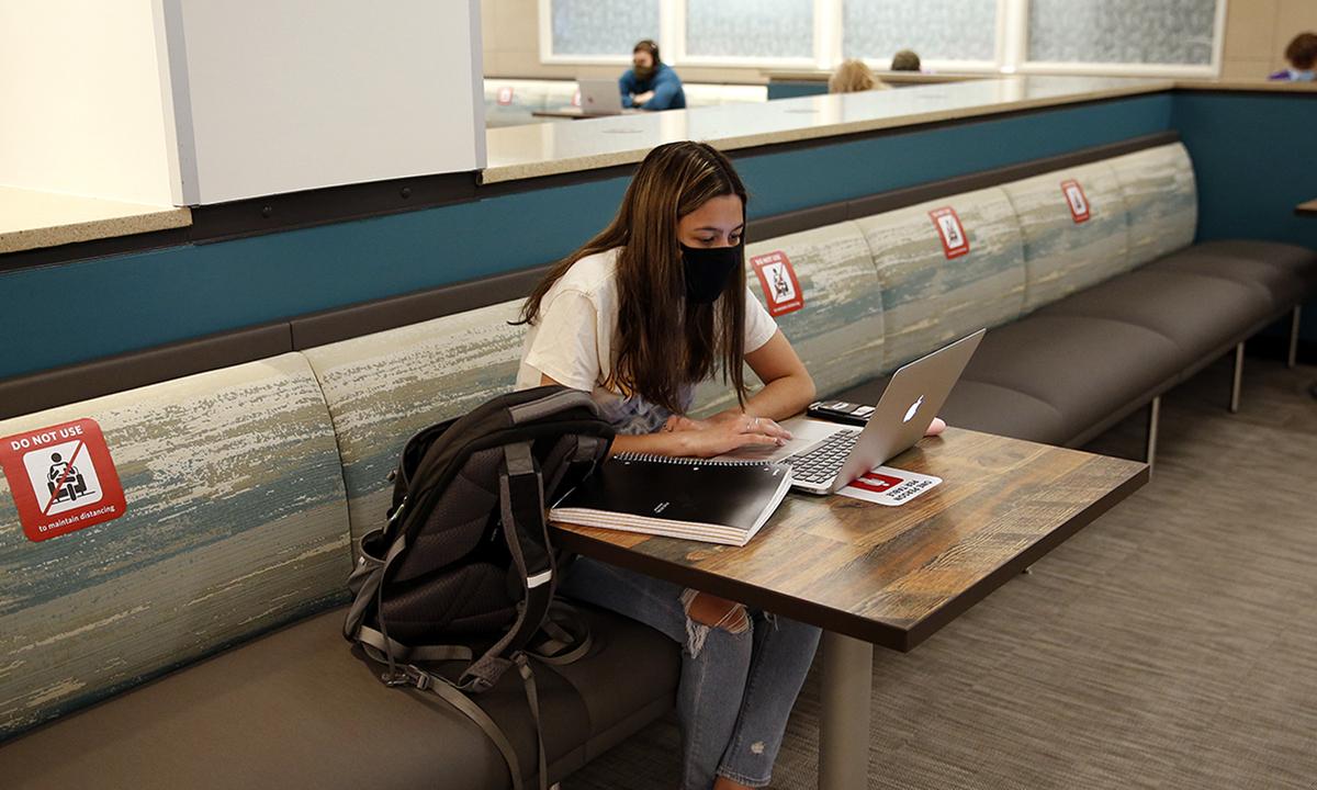Một sinh viên đeo khẩu trang ngồi học một mình tại khuôn viên trường đại học ở Boston, bang Massachusetts hồi tháng 9/2020. Ảnh: Boston Globe.