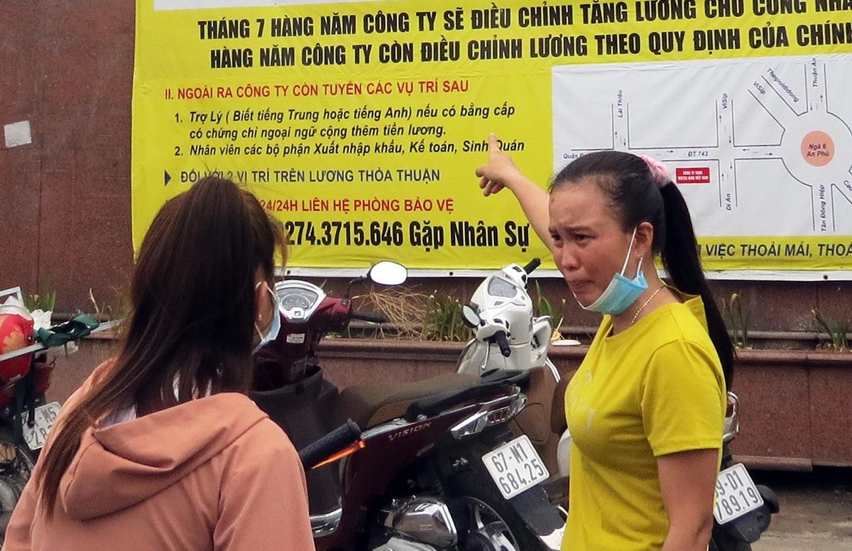 Hai nữ công nhân đọc thông tin tuyển dụng của Công ty TNHH Virtue King, chiều 2/4.  Ảnh: Lê Tuyết.