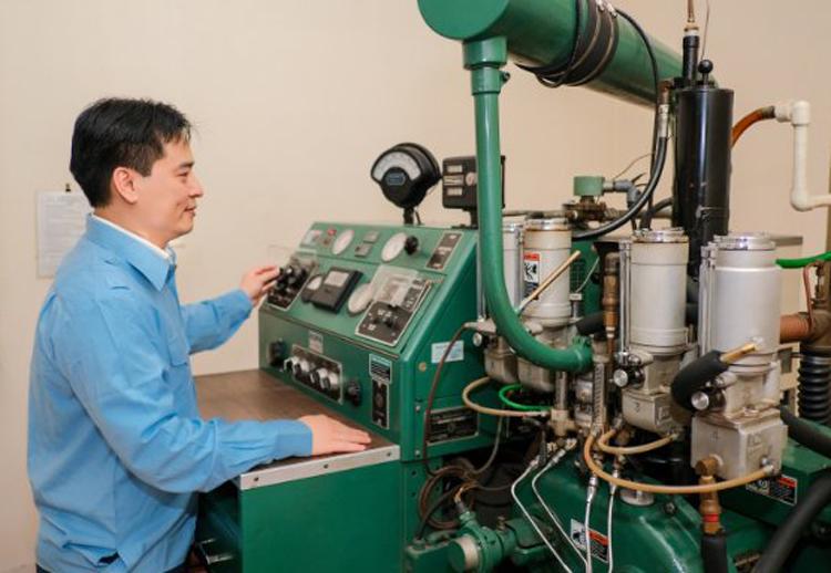 Ông Nguyễn Tuấn Tú vận hành thiết bị xác định trị số octan cho xăng. Ảnh: TĐC.