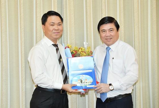 Chủ tịch UBND TPHCM Nguyễn Thành Phong (phải) trao quyết định cho ông Trần Hoàng Quân. Ảnh: SGGP.