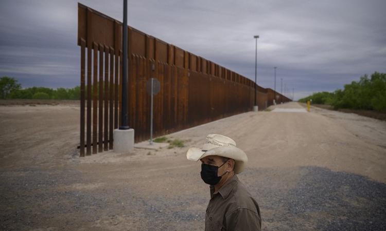 Một chủ trang trại đứng trước bức tường biên giới dang dở ở thành phố Roma, bang Texas, Mỹ hôm 28/3. Ảnh: AFP.